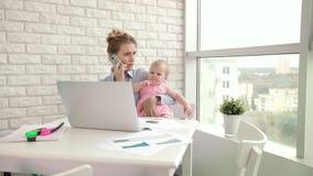 Affärsmodern med behandla som ett barn den talande mobiltelefonen Kvinna som arbetar med barnet arkivfilmer
