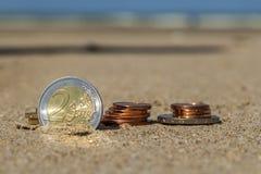 Affärsmynt på ferie i sanden på stranden, Nordsjön Arkivfoton