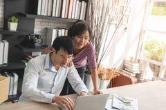 Affärspar som kontrollerar materielet i deras online-hem- affär royaltyfri fotografi