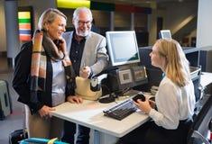 Affärspar som ser det hållande passet för personal på flygplatsen Che royaltyfria foton