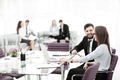 Aff?rspar som talar, medan sitta p? ett skrivbord i ett modernt kontor arkivbilder