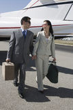 Affärspar som tillsammans går på flygfältet Royaltyfri Bild