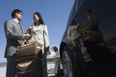 Affärspar som tillsammans står på flygfältet Royaltyfri Foto
