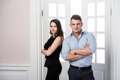 Affärsparet står tillsammans och ler i kontoret för dörröppningshemmiljövinden Fotografering för Bildbyråer