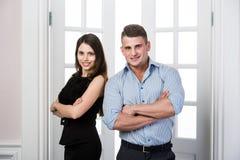 Affärsparet står tillsammans och ler i kontoret för dörröppningshemmiljövinden Arkivfoto