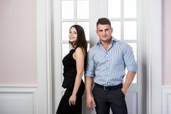 Affärsparet står tillsammans och ler i kontoret för dörröppningshemmiljövinden Arkivfoton