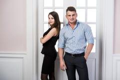 Affärsparet står tillsammans och ler i kontoret för dörröppningshemmiljövinden Arkivbild