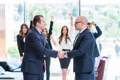 Affärspartnerhandshaking, når underteckning av avtalet arkivfoton