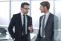 Affärspartners diskuterar att stå i kontoret royaltyfri foto