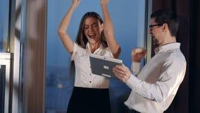 Affärspartners firar nyheterna som mottas från en minnestavla lager videofilmer