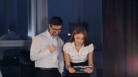Affärspartners firar seger, när jämför bärbar dator- och minnestavladata arkivfilmer