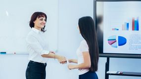 Affärspartners - kvinnan skakar händer efter en lyckad presentation på växande schema för vonen arkivfoton
