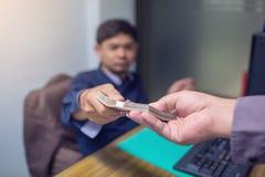 Affärspartners sänder bedräglig kassa till entreprenörer vars manliga affärsmän som accepterar mutor i kontoret arkivfoto