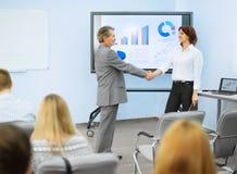 Affärspartners skakar händer efter en presentation arkivbilder