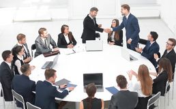 Affärspartners skakar händer på samtalen nära den runda tabellen Arkivbild