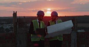 Affärspartners som analyserar konstruktionsplanet av arbets-, bärasäkerhetsutrustning, fantastisk himmel och stadssikt arkivfilmer
