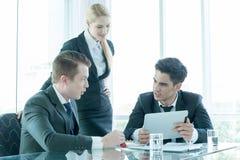 Affärspartners som diskuterar dokument och idéer på mötet Arkivbild