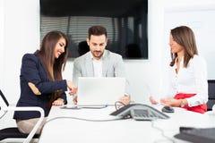 Affärspartners som diskuterar dokument och idéer på mötet arkivfoto