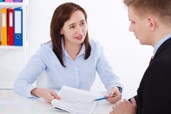 Affärspartners som diskuterar dokument och strategiskt hyvla på mötet Kontorsbakgrund Affärskvinna och affärsman arkivbilder