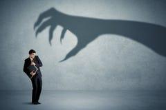 Affärsperson som är rädd av ett stort gigantiskt jordluckrareskuggabegrepp Arkivfoto