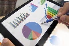 Affärsperson som analyserar finansiell statistik som visas på minnestavlaskärmen med en penna Royaltyfria Foton