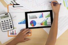 Affärsperson som analyserar finansiell statistik som visas på minnestavlaskärmen med en penna Royaltyfri Bild