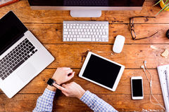 Affärsperson som arbetar på kontorsskrivbordet som bär den smarta klockan Royaltyfri Foto