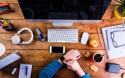 Affärsperson som arbetar på kontorsskrivbordet som bär den smarta klockan Arkivbilder