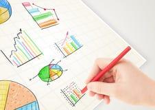 Affärsperson som drar färgrika grafer och symboler på papper Arkivfoto