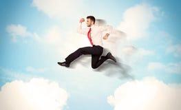 Affärsperson som hoppar över moln i himlen Royaltyfri Bild