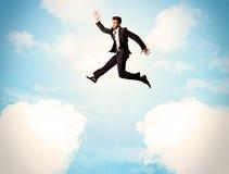 Affärsperson som hoppar över moln i himlen Arkivfoto