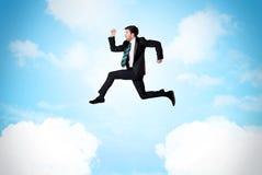 Affärsperson som hoppar över moln i himlen Fotografering för Bildbyråer