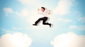 Affärsperson som hoppar över moln i himlen Royaltyfria Bilder
