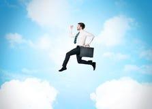 Affärsperson som hoppar över moln i himlen Royaltyfri Fotografi