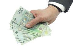 Affärspersonen räcker hållande polska pengar som isoleras på vit Arkivbild