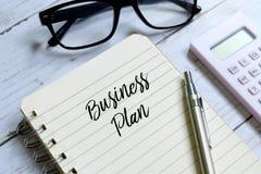 Affärsplan som är skriftligt på en anteckningsbok royaltyfri bild