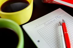 Affärsplanläggning med kaffe, anteckningsboken, sketchbooken och penna två på trätabellen för mörk brunt Royaltyfri Fotografi