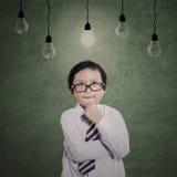 Affärspojke som tänker under lampor Fotografering för Bildbyråer