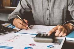 Affärsredovisning, affärsman som använder räknemaskinen med budgeten arkivfoton