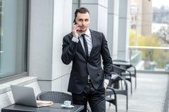 Affärssamtal En allvarlig ung man i formella kläder som rymmer en phon Royaltyfria Bilder