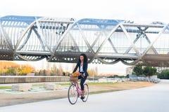 Affärssvart kvinna som rider en tappningcykel i staden Arkivfoton