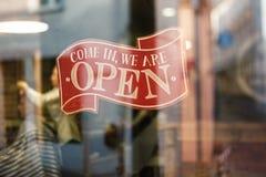Affärstappningtecknet, som säger kommet i oss, är öppet på barberare- och hårsalong shoppar fönstret - bild av abstrakt suddighet arkivfoto