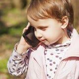 Affärstelefonkonversation Härlig affärsbarnflicka s royaltyfria foton