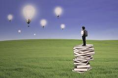 Affärsungeställning på böcker som ser utomhus- lightbulbs Royaltyfri Bild