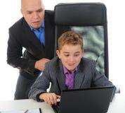 affärsmanbärbar dator genom att använda barn Arkivfoton