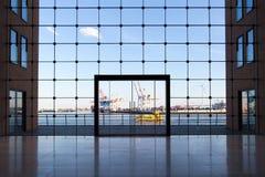 Aff?rsbyggnad i Hamburg med stora f?nster och en sikt av den ber?mda hamnen arkivbilder