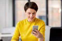 Aff?rskvinna med smartphonen som arbetar p? kontoret royaltyfri foto