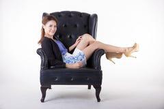 Aff?rskvinna som kopplar av i en stol arkivbild