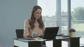 Aff?rskvinnah?lerid?liga nyheter Allvarlig frilans- kvinna som arbetar på bärbara datorn arkivfilmer