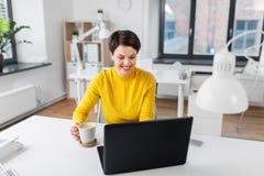 Aff?rskvinnan med b?rbara datorn dricker kaffe p? kontoret arkivfoto
